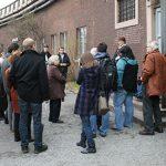 Besuchergruppe auf dem ehemaligen Appellplatz des KZ Drütte, vor der Gedenkstätte, 2013. Foto: Elke Zacharias, Arbeitskreis Stadtgeschichte e.V.